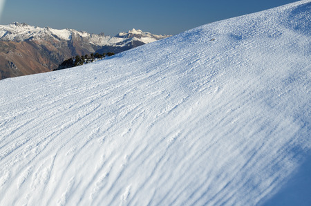 piste: Snow surface of the piste with many skiing trails are photographed in the winter mountains. Stock Photo