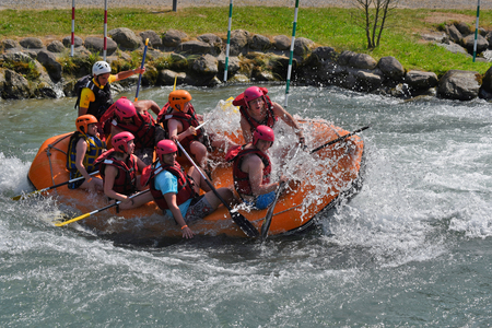 whitewater: Pau, France - June 06 2015: A raft is moving across whitewater riffles at Pau Pyrenees White Water Stadium.