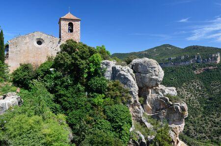 verdure: The ancient church is extant on the steep slope overgrown with lush verdure in the Prades Mountains.