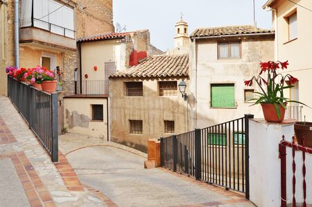 spanish houses: The steep street of the overhanging houses is decorated with flowers, rails and floor tiles in the old part of the Spanish town El Pinell de Brai. Stock Photo