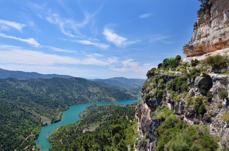 calcareous: Prades mountains is a large calcareous mountain massif heavily forested. There are the river Embalsa with the artificial lake in the green valley.