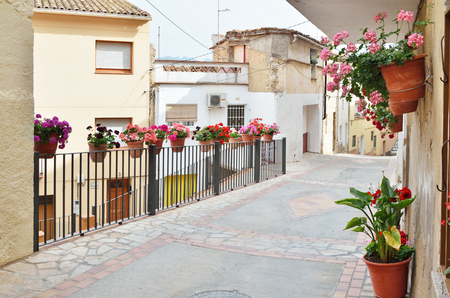 overhanging: The steep street of the overhanging houses is decorated with flowers, rails and floor tiles in the old part of the Spanish town El Pinell de Brai. Stock Photo