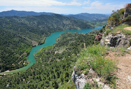 forested: Prades mountains is a large calcareous mountain massif heavily forested. There are the river Embalsa with the artificial lake in the green valley.
