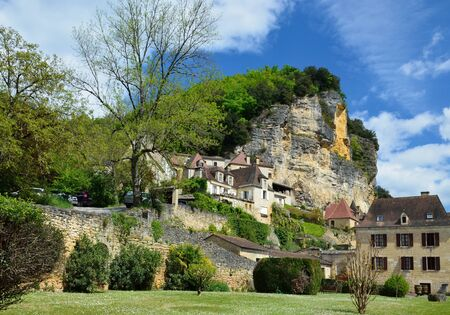 lush foliage: La Roque Gageac is one of Frances most beautiful villages.The stone yellow houses with the typical roofs spread up the steep hill overgrown with lush foliage. Stock Photo