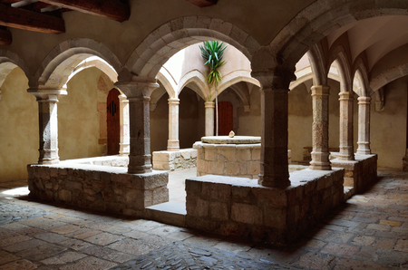sante: There is a sunlit patio with a stone well inside of the Spanish cloister Sante Creus.