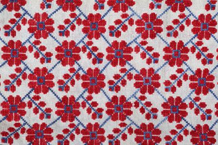 punto cruz: La pasada de moda bordados hechos a mano es fotografiado de cerca. La red de motivos florales se hace de punto de cruz en el pa�o de andar por casa.