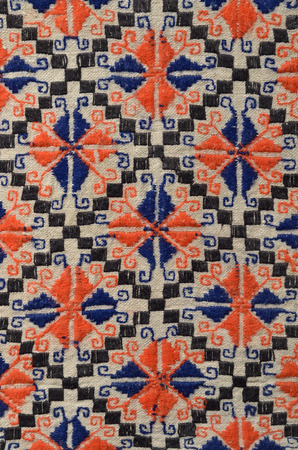 lozenge: The old handmade embroidery is photographed closely. The red and blue stars or flowers in the black rhombus are embroidered by the straight, rolling and running stitch.