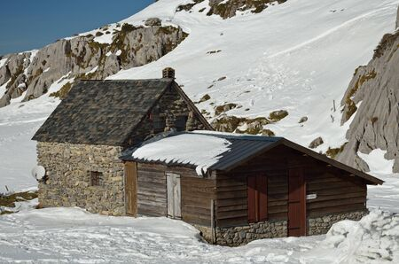 outbuilding: A small stone cottage with an outbuilding is on the mountain slope covered by snow.