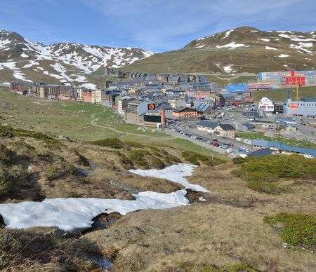 pas: Pas de la Casa is a town lying on the gentle slopes in Andorra. In the foreground there are a small stream and remains of snowfields.