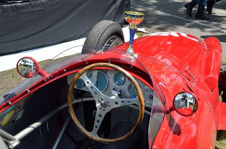 curio: The red vintage bolide is photographed with the goblet on the capote at racing Grand Prix Historique. Editorial