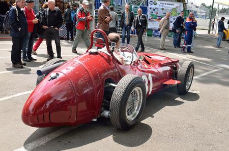 bystanders: Pau, France - May 24 2015: Participant of Grand Prix Historique drives his bolide racing car past spectators.