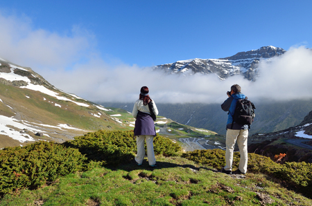 cirque: Two tourists are standing in the hill and photographing the cirque of Troumouse through the clouds.