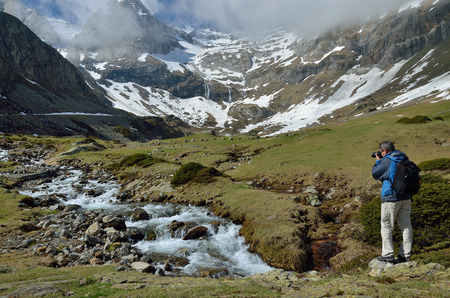 cirque: The tourist is standing in the hill and photographing the cirque of Troumouse. The mountain stream is rapidly flowing on the stone bed. Stock Photo