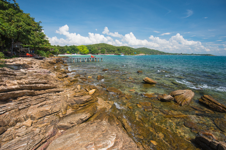 koh samet: Wild stone western coast of Ko Samet Island is photographed in the gulf of Thailand, Rayong. There is a remote sand beach in the cosy bay in the background. Stock Photo