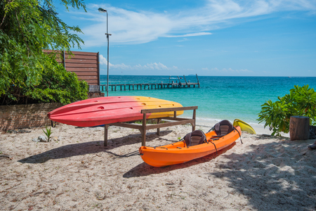 koh samet: Two modern boats are photographed in sandy beach overgrown with tropical lush foliage in the cozy bay of Ko Samet island.