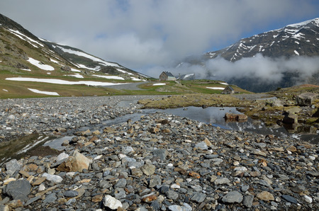 cirque: The mountain stream is flowing on the plateau in the cirque of Troumouse. In the foreground there are many stones of the riverbed.