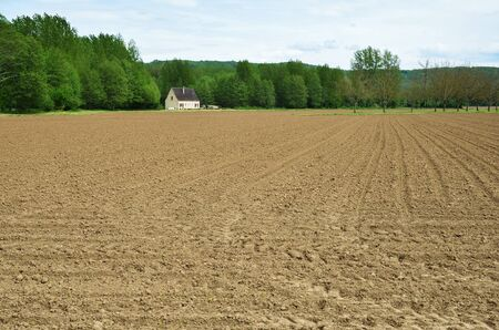 farmstead: The field is ploughed. In the background there is the remote farmstead under the green forest.