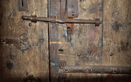 batten: The big metal lock with a latch on the wooden surface of the ancient batten door