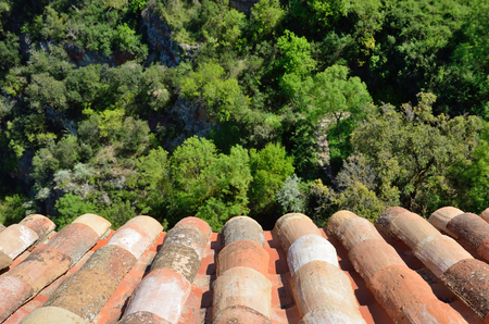 barrel tile: Traditional old tiled roof is made from locally available materials such as terracotta. It is photographed above the green lush foliage of summer forest.