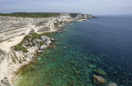 overhang: There are the white overhang cliffs, blue transparent water and limestone rocks in the seashore of the Bonifacio. Stock Photo