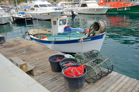 fishing rig: Bonifacio, France - April 14 2016: The small fishing boat is moored near the wooden berth at the port of Bonifacio town, Corsica.