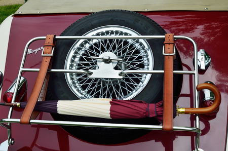 strapped: Pau, France - May 24 2015: The old-fashioned automobile Morgan is presented at the exhibition during Grand Prix Historique. There are a reserve wheel, an umbrella strapped with the leather belts on the luggage grid in the backside of the retro automobile
