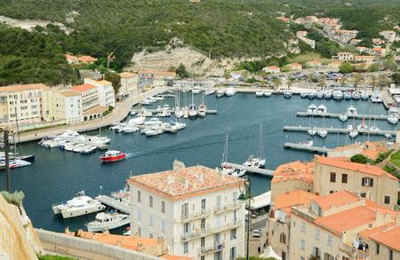 literas: Hay muchos diversos buques en el puerto y los edificios residenciales en la estrecha plataforma en la parte inferior de Bonifacio. Foto de archivo