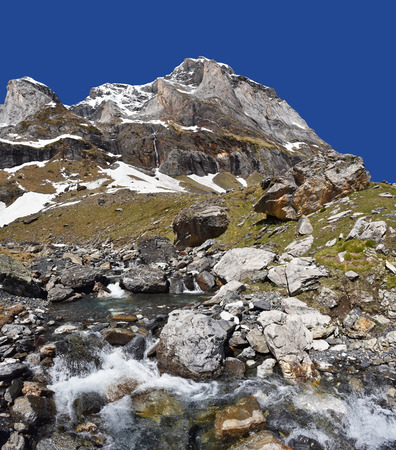 The stream is rapidly flowing on the mountain slope in the cirque of Troumouse.