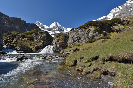 The mountain stream ruisseau du Cot is rapidly flowing on the plateau from the cirque of Troumouse. Stock Photo