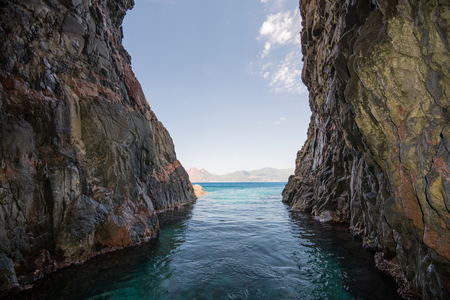 The narrow gap is situated between steep cliffs plunging in the blue transparent water of the calm sea. The coast of the Golfe de Porto is one of Corsican most famous landscapes. Imagens