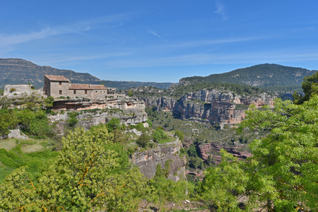 extant: The ancient small village is extant on the cliffs edge in the Prades mountains. Stock Photo