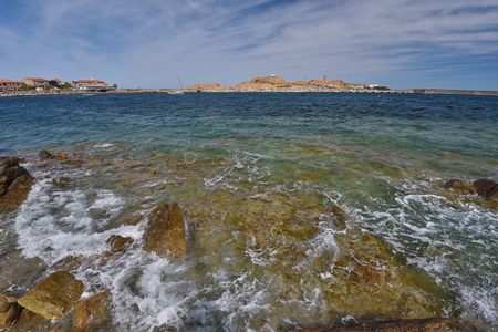 There are transparent shoal water with waves and the rocky coast in the Corsican seashore near the town LIle Rousse. Ile de la Pietra is a remote big rocky red island with an ancient Genoese tower and a lighthouse in the background. Stock Photo