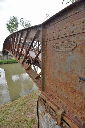 The old rusty bridge is on the navigable canal de Jonction at the French town Salleles dAude. This is a part of the La Nouvelle branch of the Canal du Midi.