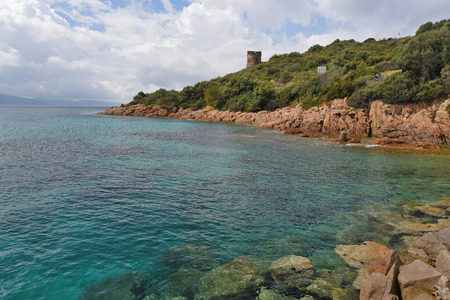 There are transparent water and the reddish rocks overgrown with maquis (evergreen scrubs) in the bay of Sagone.