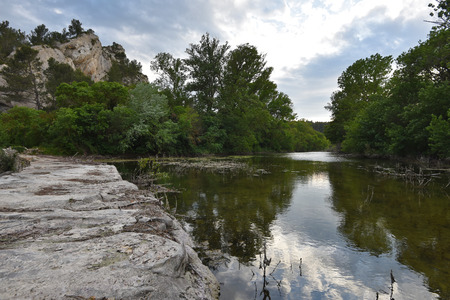 A small reservoir of still water is formed artificially by the stone dike near the rock. Its banks are forested.