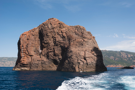 Volcanic red rock emerges from the transparent sea in the natural park Scandola. Stock Photo