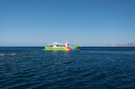 The modern motorboat with visitors is floating on the Mediterranean sea.