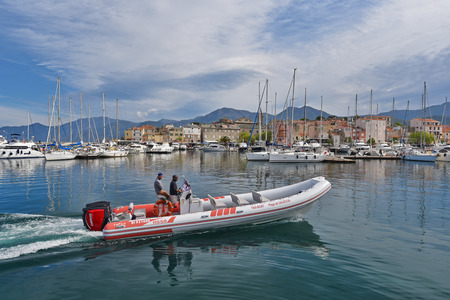Saint-Florent, France - April 18 2016: A pleasure-boat is floating along the berth with many modern vessels in the Corsican port Saint-Florent.