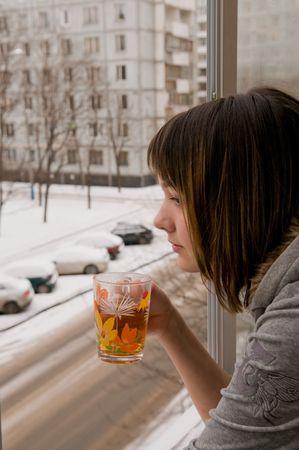 ventanas abiertas: Gastos de la ni�a en un balc�n a una ventana abierta y bebidas de t� caliente. Detr�s de una ventana de invierno. Foto de archivo