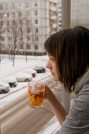 balcony window: The girl costs on a balcony at an open window and drinks hot tea. Behind a window winter.