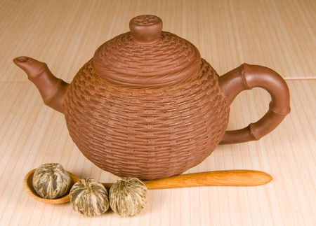 wooden lid: Clay tea-pot and green tea in a wooden spoon on a bamboo tile Stock Photo