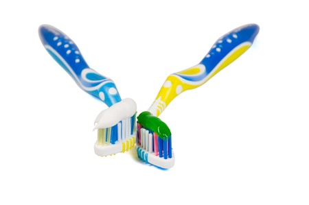 Two tooth-brushes with different paste on a white background photo