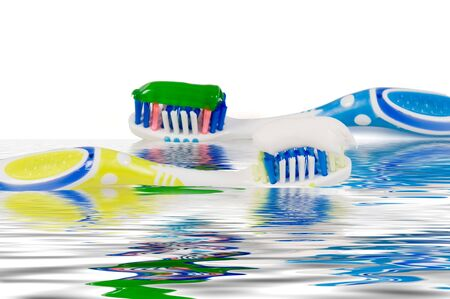 Two tooth brushes in water with a reflection photo