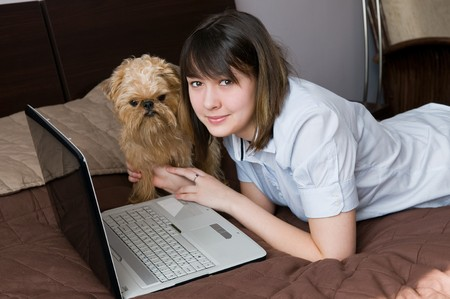 The sixteen-year girl with a dog and the laptop on a bed photo