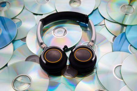 cdrom: Black big headphones against disks of CD and DVD