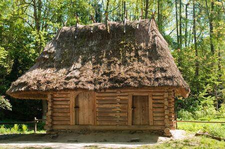 An old, neglected, wooden house is in the Ukrainian village. House from wooden logs with a thatch roof. Stock Photo