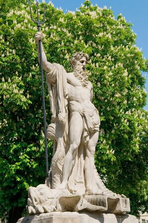 statuary: Old sculpture of Neptune on a background a flowering chestnut Stock Photo