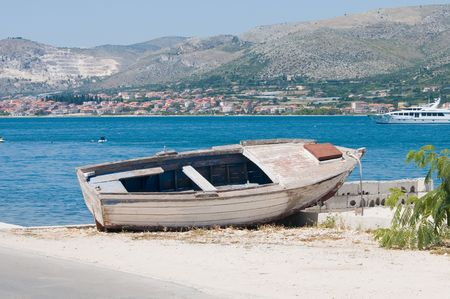 An old wooden boat costs ashore in the background   blue sea. photo