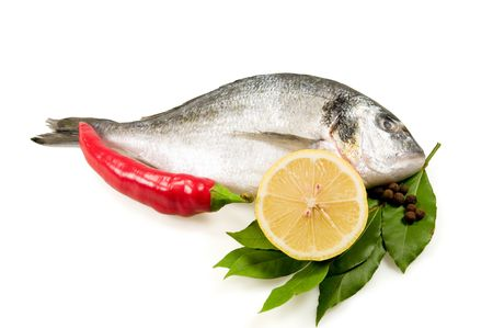 Fresh fish (dorada) and vegetables isolated on a white background.