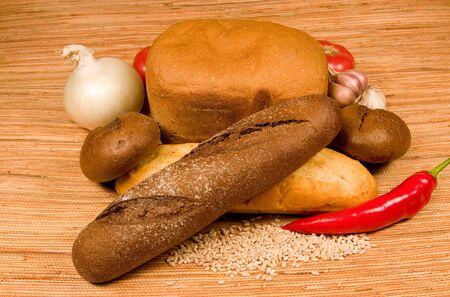 Vegetables, wheaten and rye bread on a straw cloth photo
